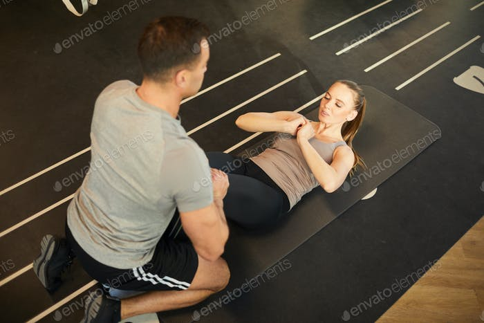 Fitness Coach Working with Woman in Gym