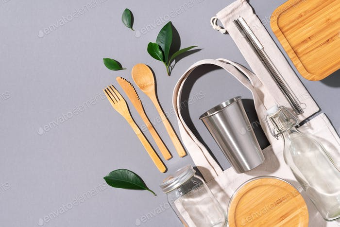 Cotton bags, glass jar, bottle, metal cup, straws for drinking, bamboo cutlery and boxes on gray