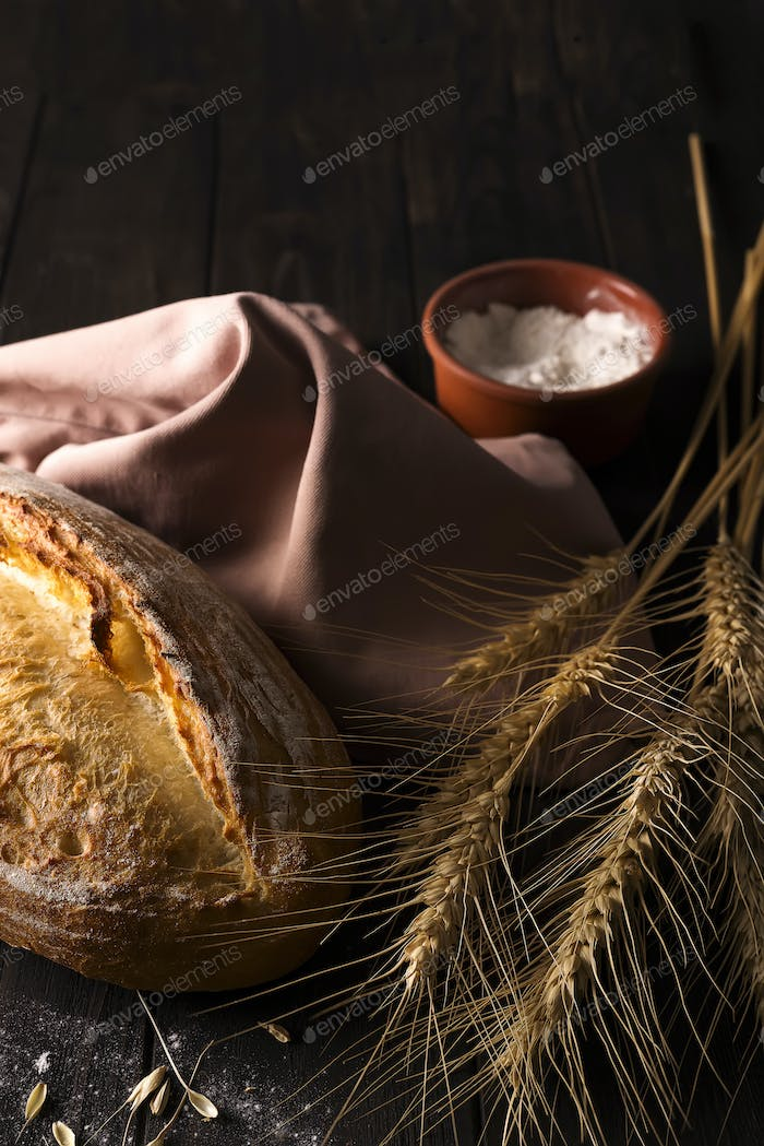 Fresh bread with wheat on wooden table