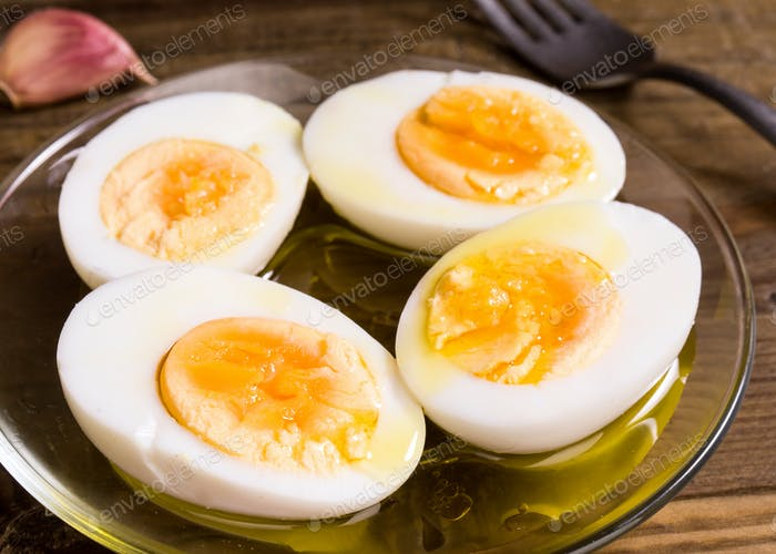 hard boiled eggs cut in half with oil and vinegar, on wooden board