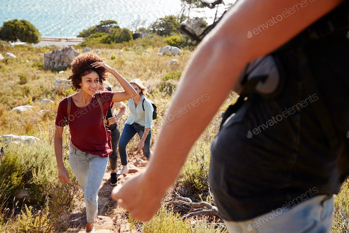 Millennial African American woman hiking by the coast with friends, selective focus