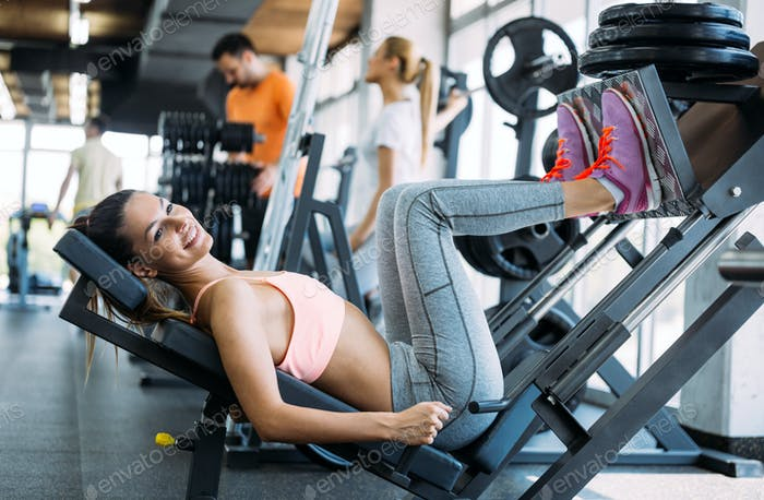 Young beautiful woman doing exercises in gym