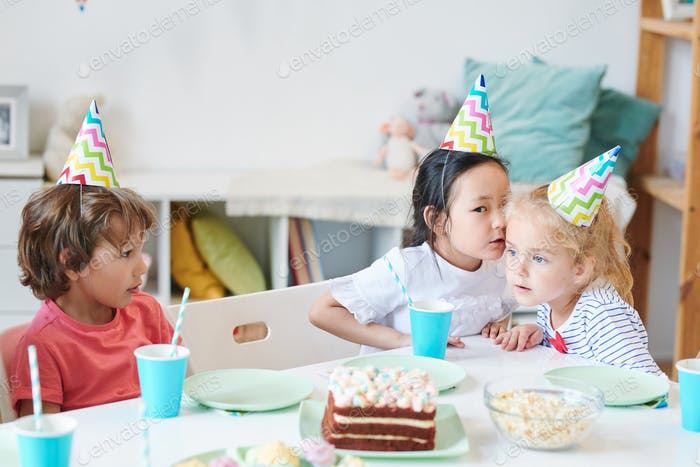One of cute girls in birthday caps whispering something to her friend
