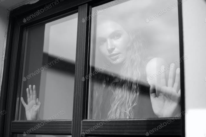 woman stands in front of window