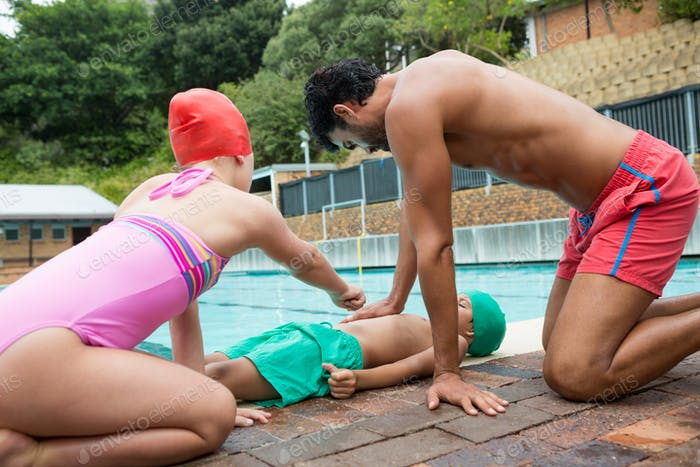 Lifeguard assisting unconscious boy while interacting with girl