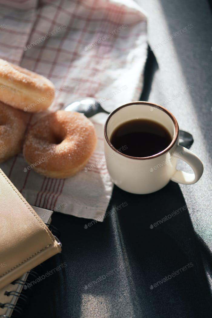A cup of black coffee and donut in the window light