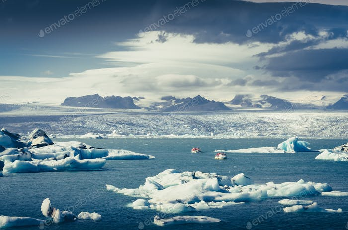 Landscape view of Jokullsarlon lagoon with floating ice and boat, Iceland