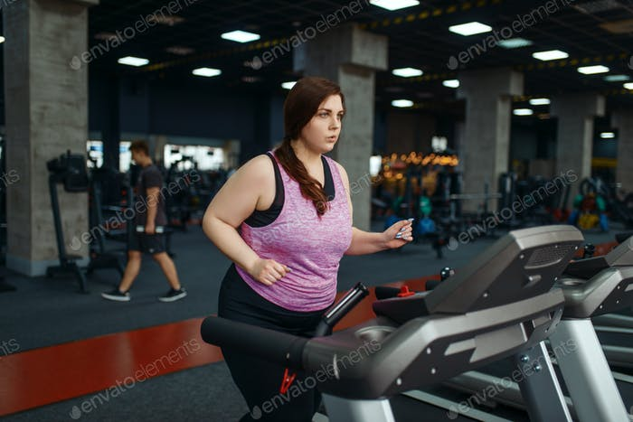 Overweight woman, exercise on treadmill in gym