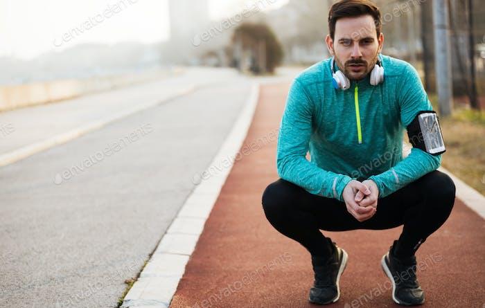 Sporty handsome man resting after jogging