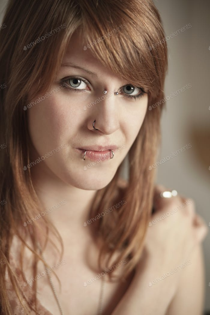 Close-up portrait of young woman with piercings