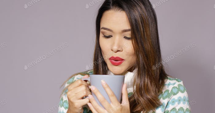 Gorgeous young woman enjoying hot coffee