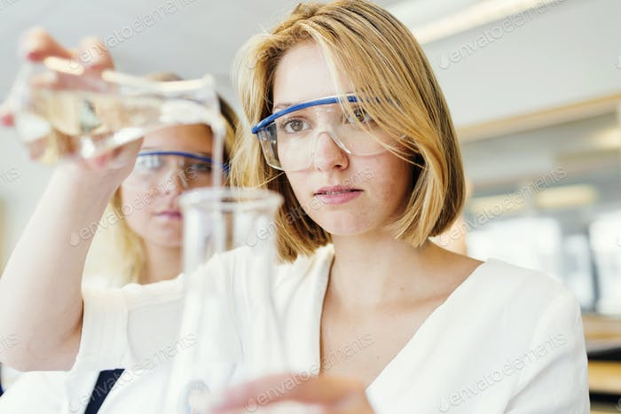 Students performing experiment in science classroom