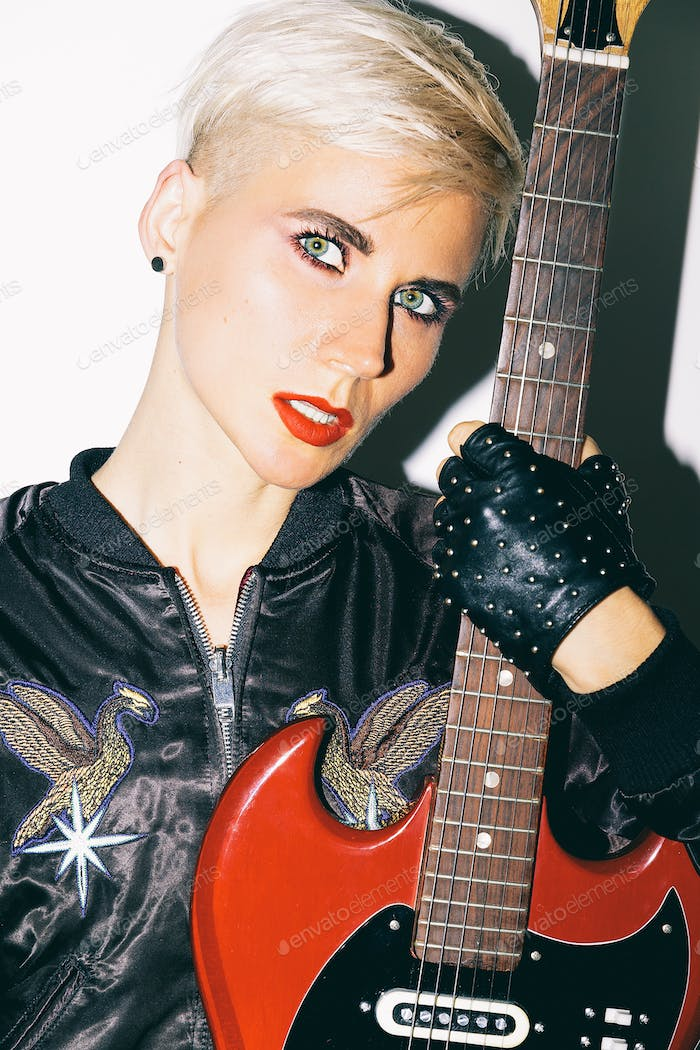 Blonde Girl with electro guitar. Rock fashion style