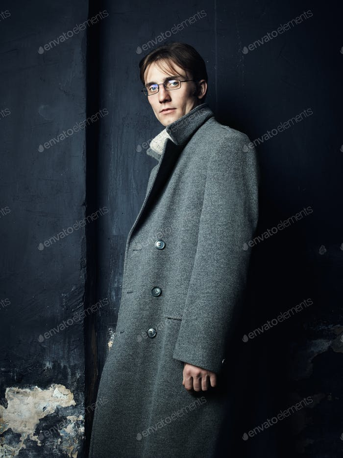Artistic dark portrait of the young beautiful man in a gray coat