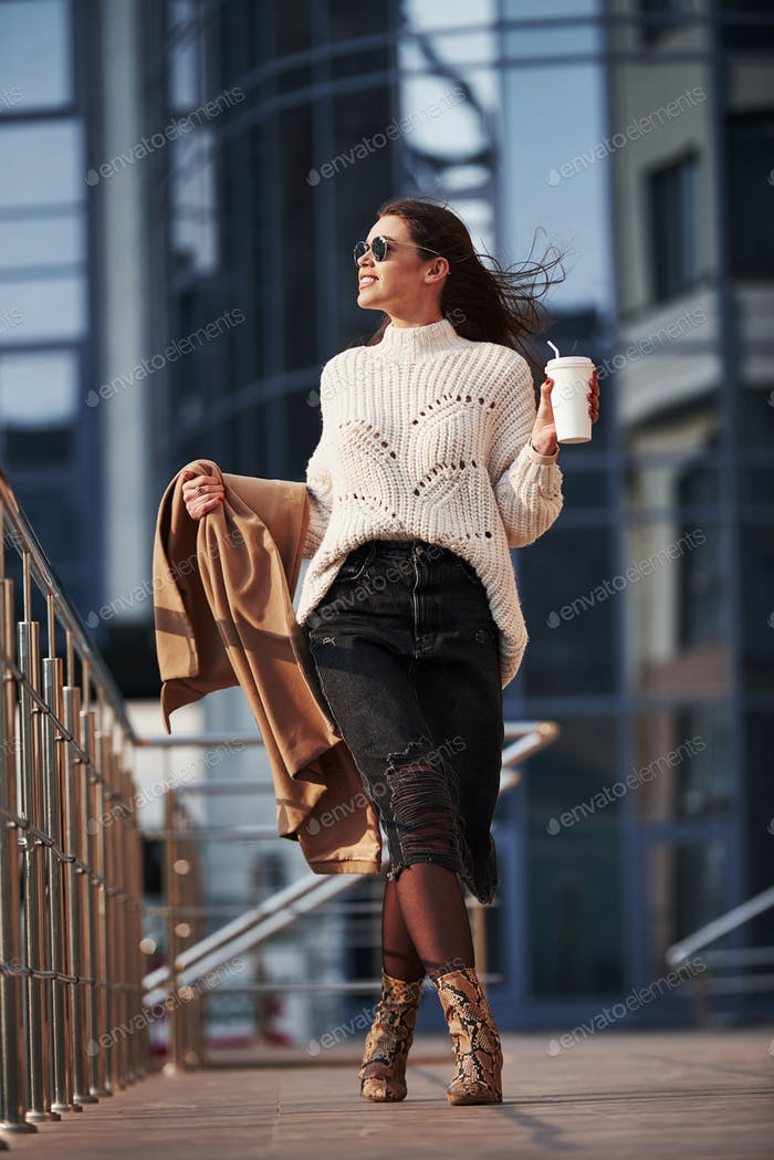 Urban life. Young beautiful girl in warm clothes have walk in the city at her weekends time