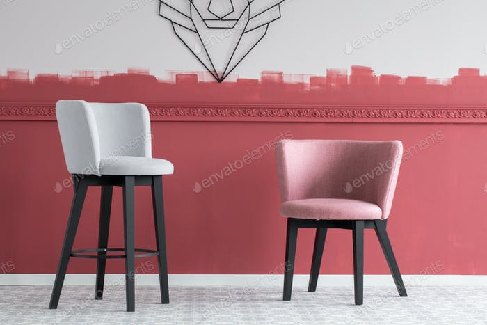 Pastel pink and grey velvet bar stools in empty interior with burgundy and white ombre wall