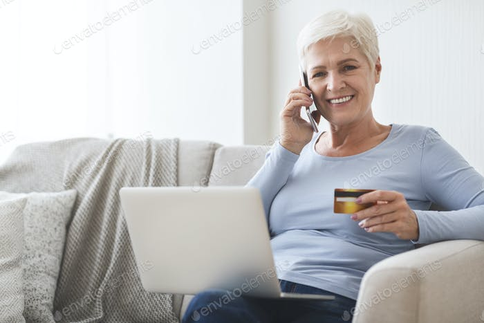 Mature lady shopping online with credit card and laptop