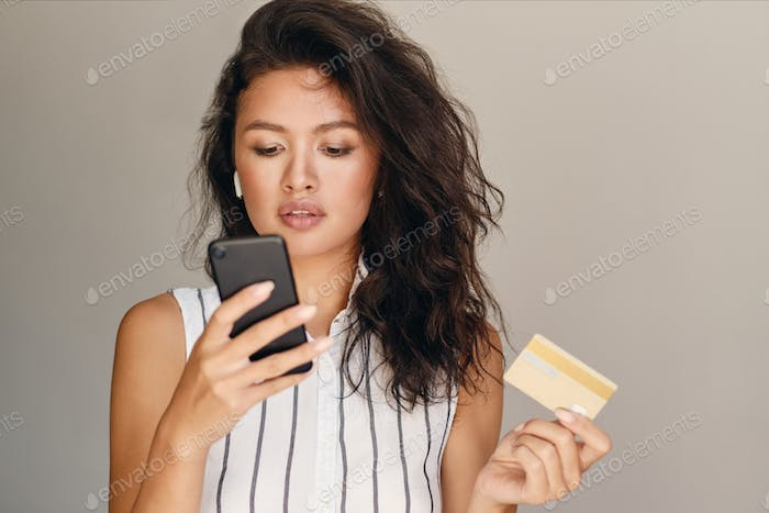 Young beautiful Asian woman with credit card confidently using cellphone over gray background