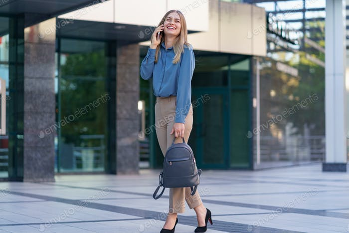 MODERN WOMAN WITH BACKPACK SPEAKING BY PHONE NEAR BUSINESS CENTER