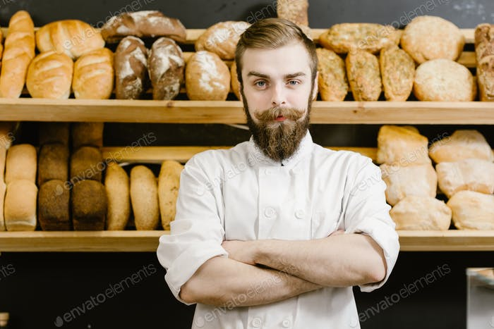 Charismatic baker stands on the background of shelves with fresh bread in the bakery