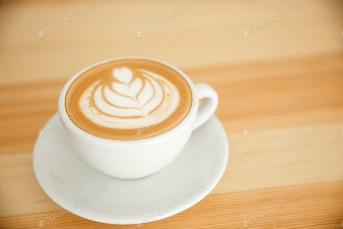 Coffee Business Concept - fresh serve hot coffee with heart latte art in modern coffee shop