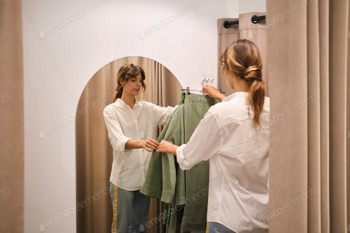 Young stylish fashion consultant thoughtfully putting clothes in dressing room for customer in store