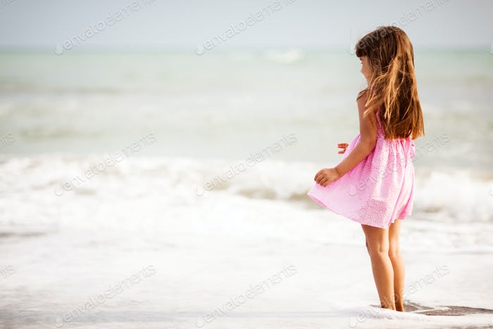 Mädchen mit braunen Haaren springen auf Meeresküste