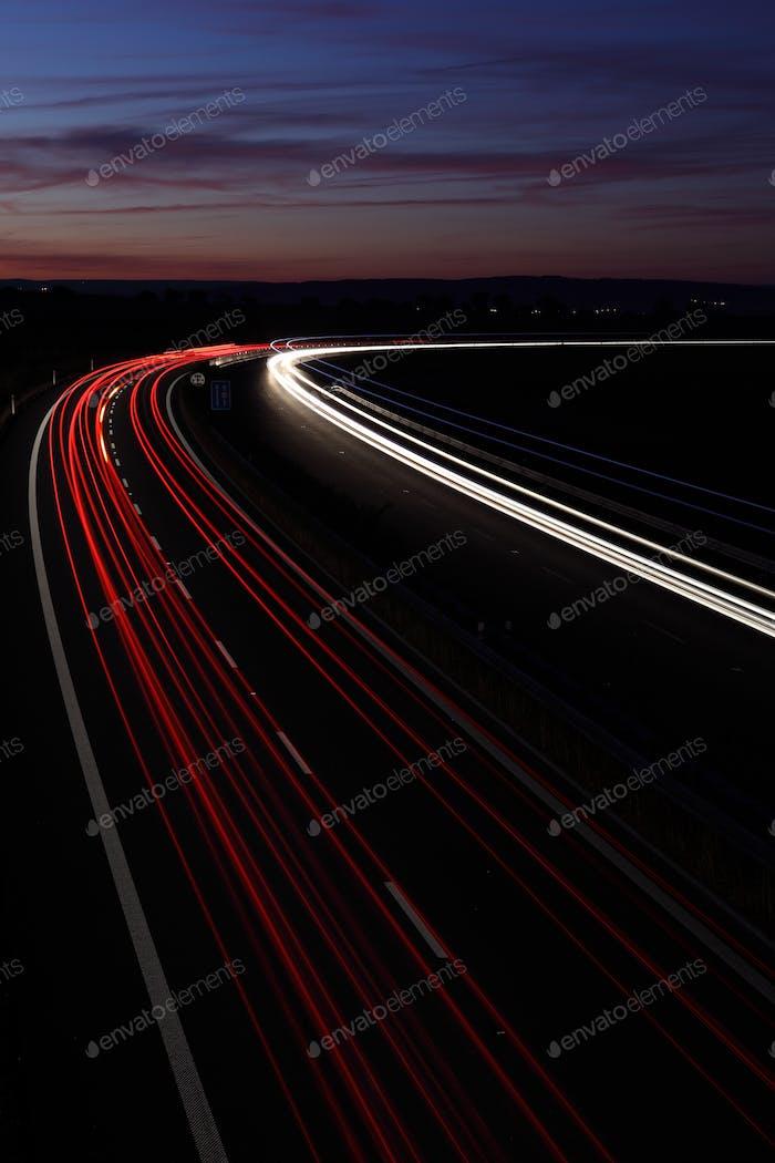 Autos in Eile bewegen sich schnell auf einer Autobahn (Speedway) in der Dämmerung