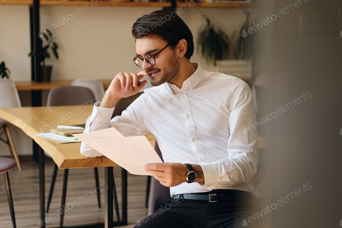 Young attractive smiling businessman in eyeglasses happily reading papers working in modern office