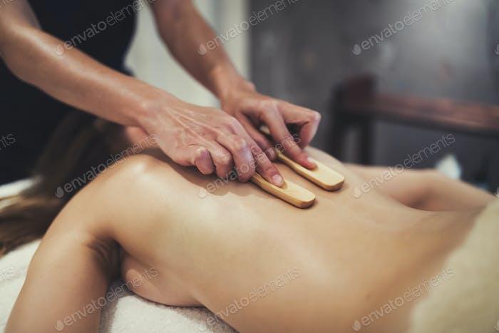 Masseur massaging female on bed