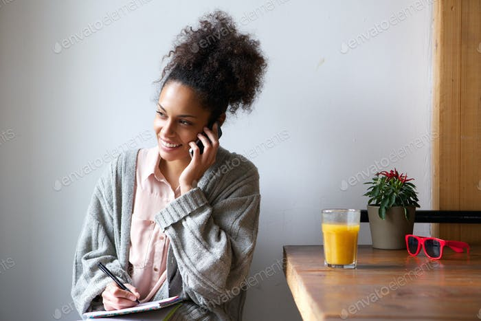 Young woman talking on mobile phone and taking notes