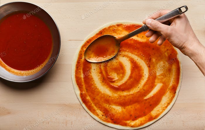 Chef hand spreading tomato paste on pizza base