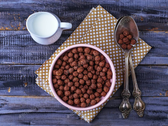 Chocolate cereal balls in bowl and milk