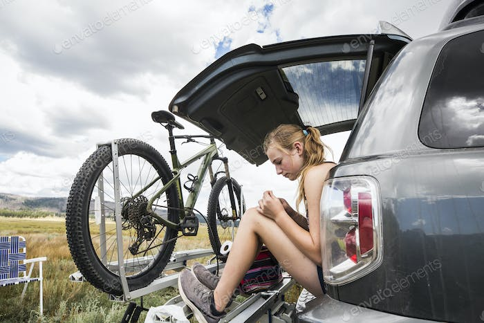 Teenage girl sitting on the tailgate of an SUV looking at vista
