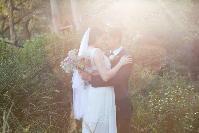 Romantic newlywed couple with eyes closed embracing in park