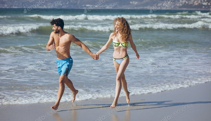 Couple holding hands and running by the oean at beach