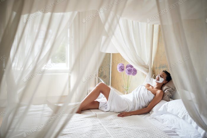 Smiling woman relaxing in  bed at home with  mask on her face.Face skin care concept.