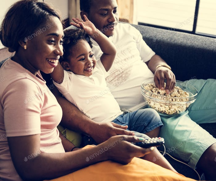 Black family eating popcorn while watching movie at home