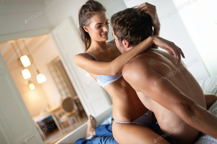 Passionate beautiful couple in bedroom enjoying foreplay