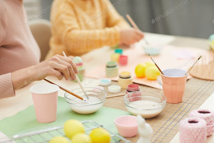 Closeup of Young Woman Hand Painting Easter Eggs with Daughter