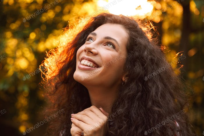 Photo closeup of brunette smiling girl 18-20 looking upward, whi