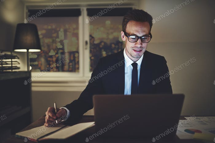 Smiling businessman working on laptop