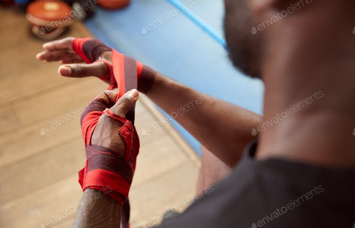 Close Up Of Male Boxer Training In Gym Putting Wraps On Hands
