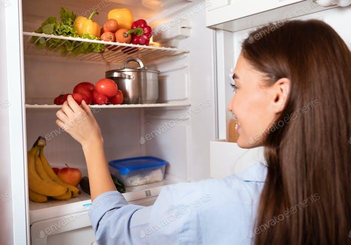 Junge Hausfrau nehmen Bio-Gemüse aus dem Kühlschrank