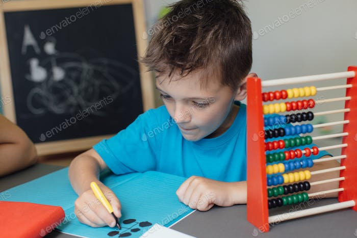 Focused schoolboy working on math homework