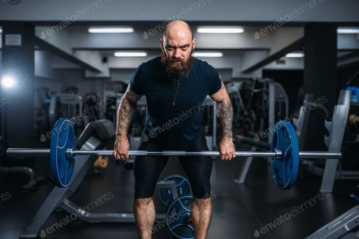 Muscular athlete in sportswear takes weight