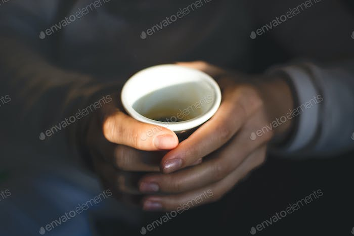 Hands holding paper cup of espresso