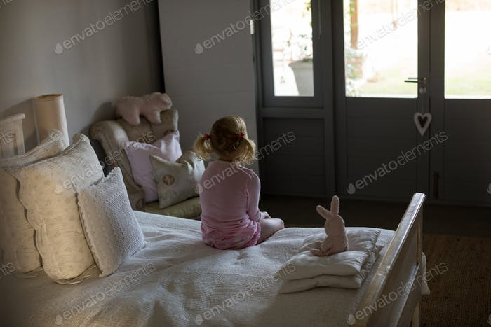 Girl sitting on bed in the bedroom at home