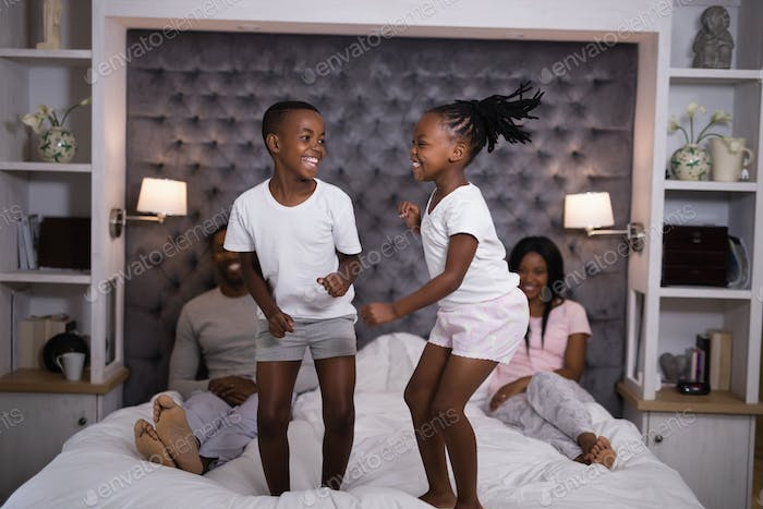 Playful siblings jumping on bed