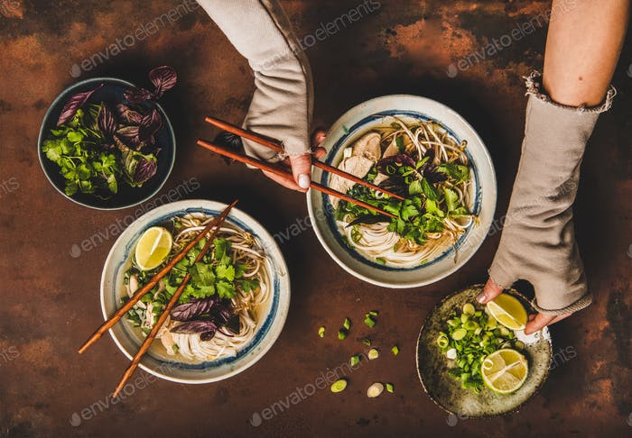Womans hands with chopsticks and lime over vietnamese Pho-Ga soup